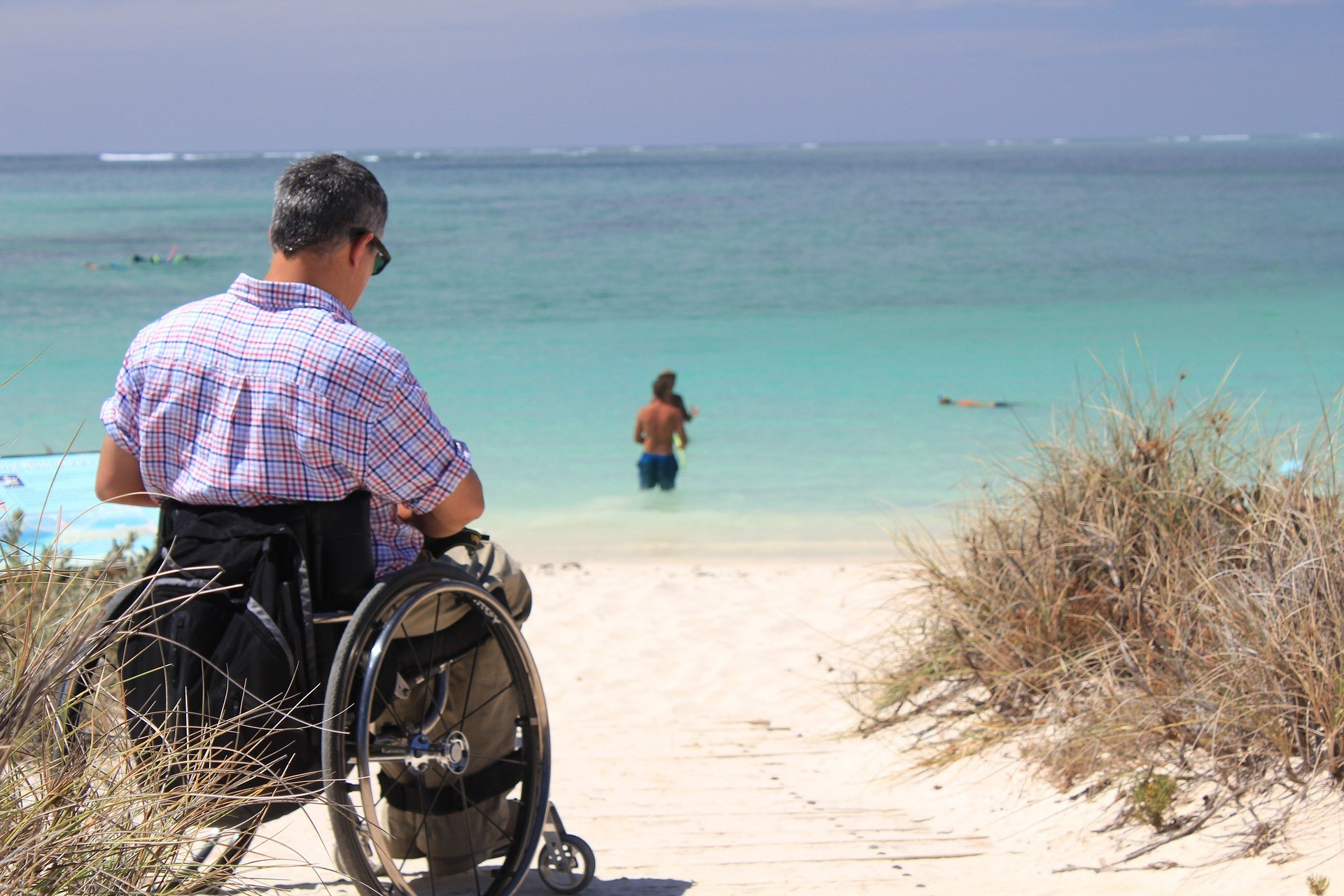 person in wheelchair at the beach
