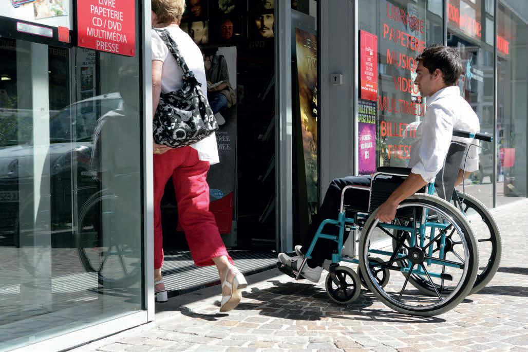 person in wheelchair entering an accessible building